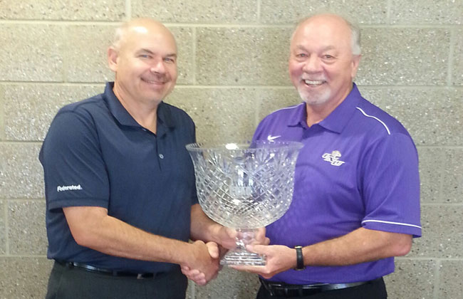 Commissioner Jeff Schimmelpfennig (left) presents ONU athletics director Gary Newsome with the 2013-14 CCAC All-Sports Cup.
